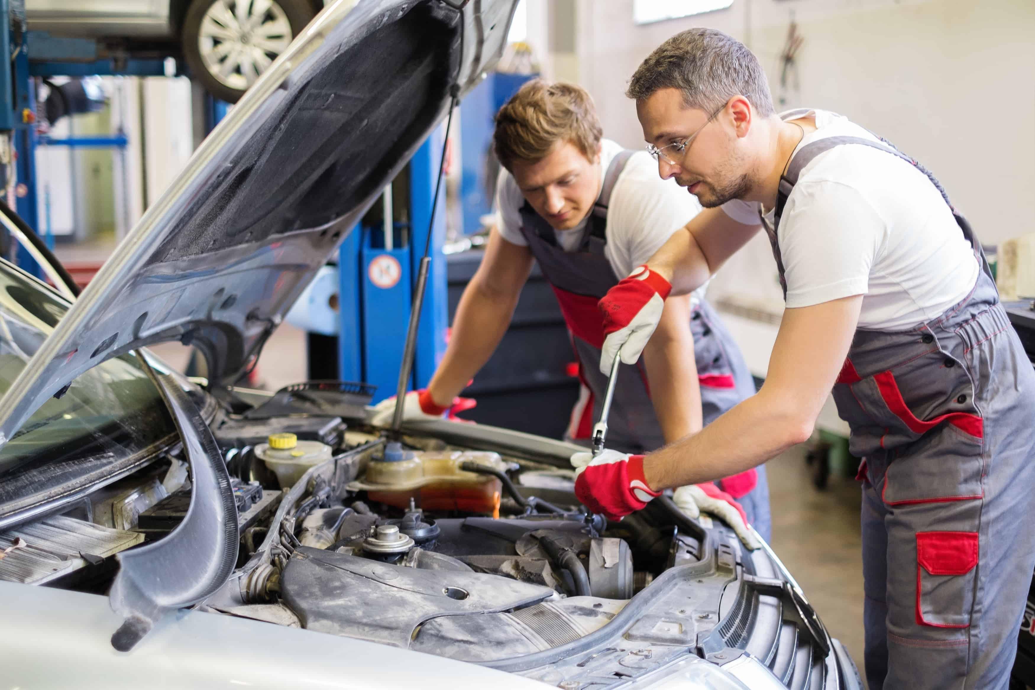 Dwóch mechaników reperuje auto, zaglądają do silnika i przewodów