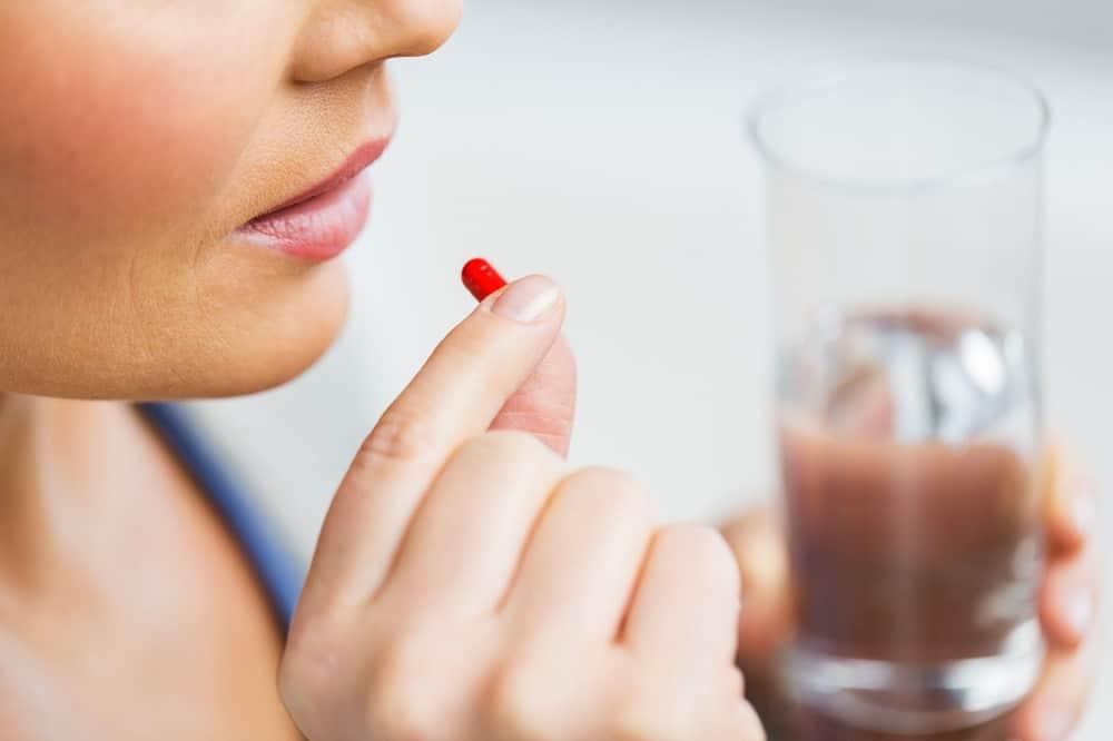 Kobieta zarzywająca leki przed podróżą