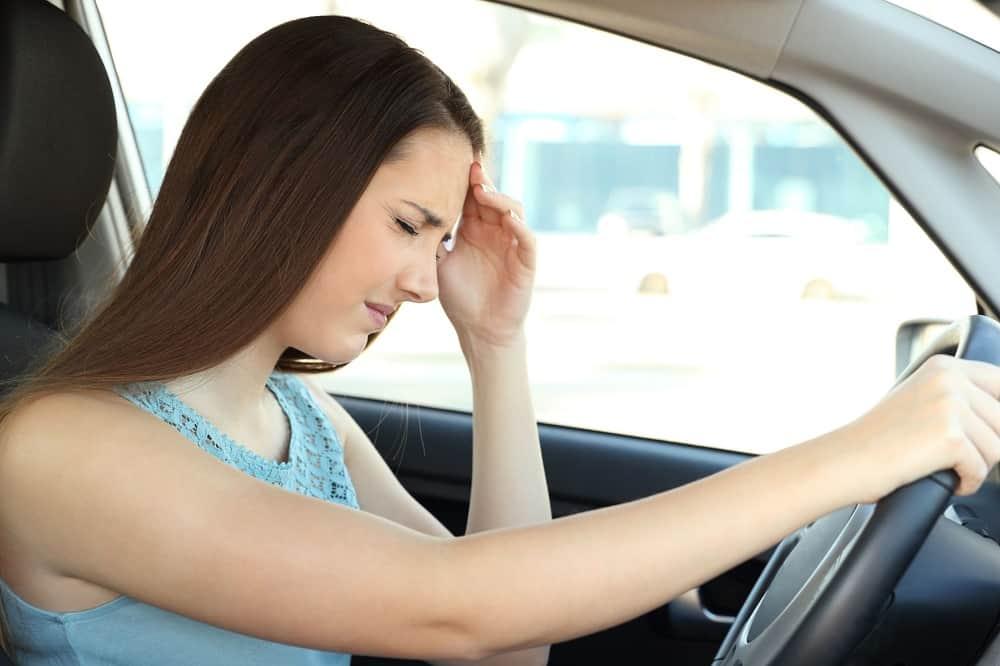 Kobieta w samochodzie trzymająca się za głowę