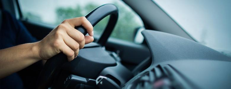 Dłonie na kierownicy auta