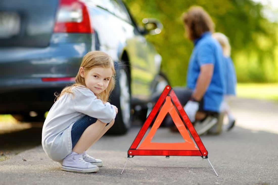 dziewczynka kuca przy trójkącie ostrzegawczym postawionym przy aucie