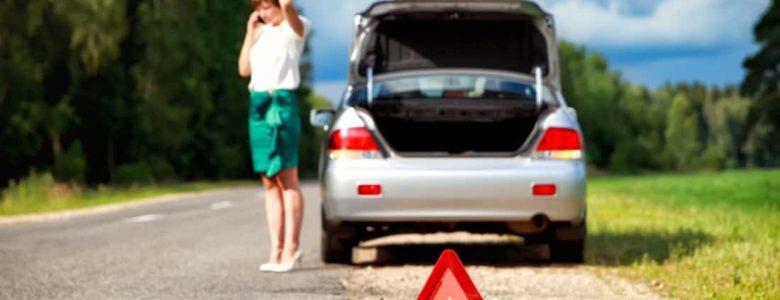 Kobieta stojąca na poboczu, z powodu brakującego paliwa w samochodzie