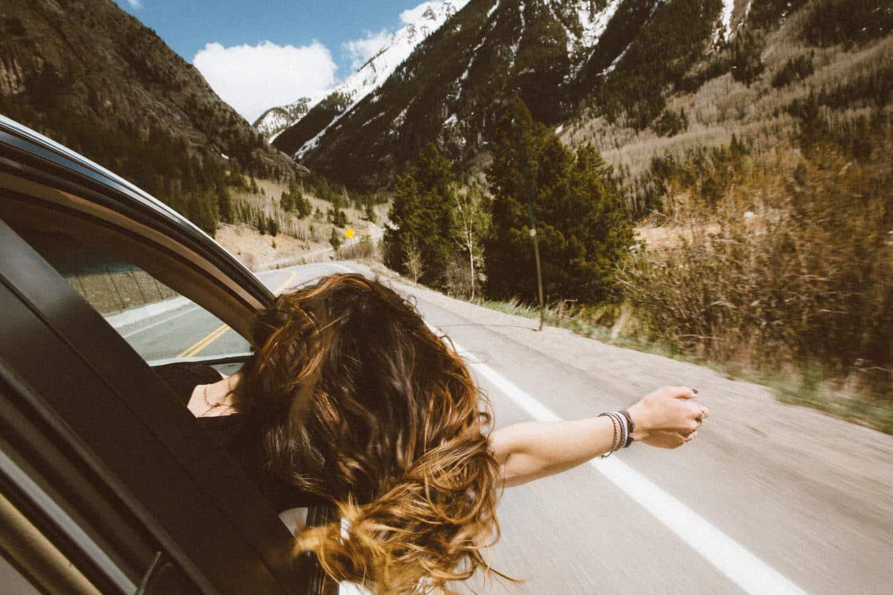 kobieta w aucie na drodze gdzieś w górach