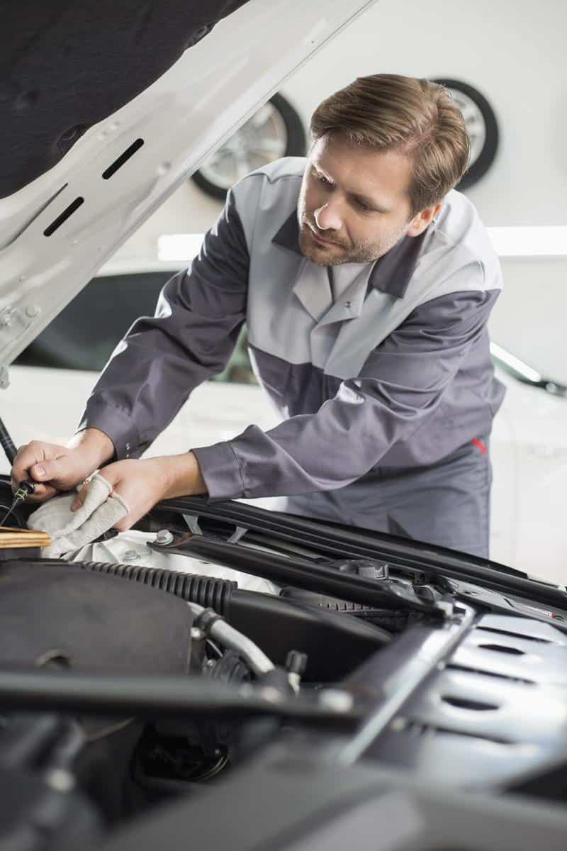 mechanik z bagnetem sprawdza olej