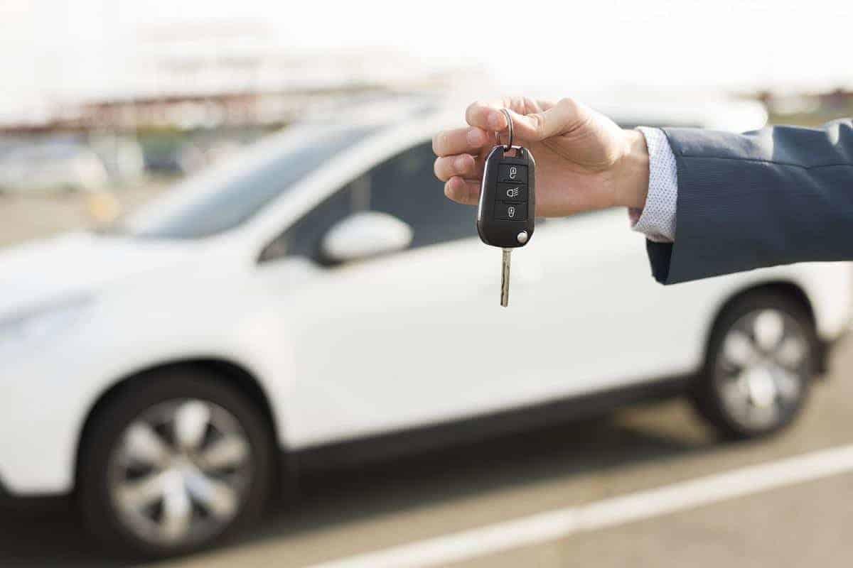 dłoń trzymająca kluczyk na tle auta