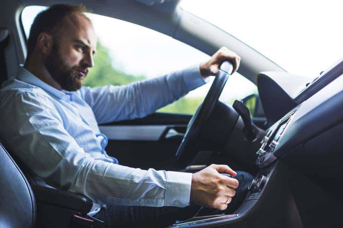 kierowca z dłonią na automatycznej skrzyni biegów